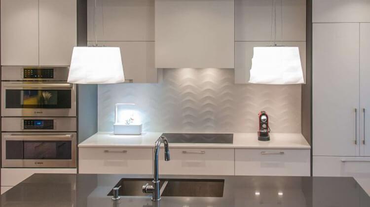 Rénovation de cuisine avec armoires blanches et luminaires suspendus